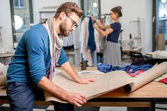 Fashion designer at the studio. Portrait of a handsome fashion designer sitting with paper sketches at the studio full of tailoring tools and clothes Stock Photo