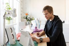 Fashion designer with tablet pc working at studio. People, technology and tailoring concept - fashion designer with tablet pc computer working at studio royalty free stock image