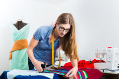 Fashion designer or tailor working in studio. Freelancer - Fashion designer or Tailor working on a design or draft and cutting fabrics with scissors Royalty Free Stock Photography