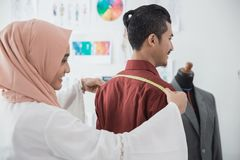 Fashion designer taking measure of customer body. Before making a custom suit Stock Photo