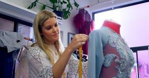Fashion designer taking measurement of dressmakers model 4k. Fashion designer taking measurement of dressmakers model in fashion studio 4k stock video footage