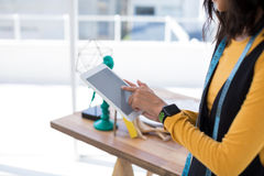 Fashion designer using digital tablet in office. Mid-section of fashion designer using digital tablet in office royalty free stock images