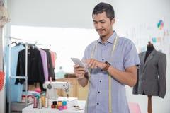 Fashion designer using mobile phone. Smiling happy fashion designer using mobile phone in his workshop Stock Photo