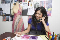 Fashion Designer Using Phone At Desk Royalty Free Stock Photos