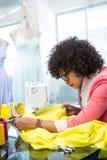 Fashion designer using sewing machine Stock Photography