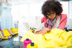 Fashion designer using sewing machine Stock Photography