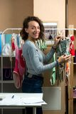Fashion designer of women`s clothing in the workshop. Nearby there is a hanger on which swimsuits are hung Stock Photos