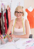 Fashion designer at work. Cheerful young fashion designer drawing sketch and smiling Stock Photos