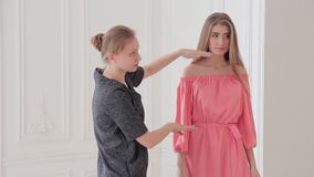 Fashion designer work with her pink summer dress on model during photo shoot stock video footage