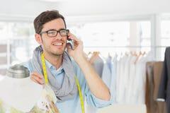 Fashion designer working on dress while using mobile phone Royalty Free Stock Image