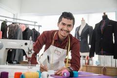 Fashion designer drawing some design. Fashion designer working in his workshop drawing some design Royalty Free Stock Photography