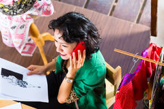Fashion designer working at home. Freelancer - Fashion designer working at home on a design or draft, she uses a mobile phone, to talk with a client royalty free stock image
