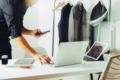 Fashion designer working with mobile phone and using laptop with. Digital tablet computer in modern studio Stock Image