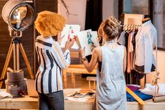 Fashion designer working at the office. Two female multi-ethnic fashion designers working with clothes drawings standing at the beautiful office with different royalty free stock photo