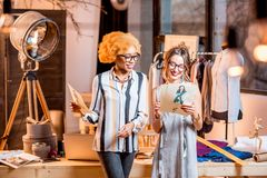 Fashion designer working at the office. Two female multi-ethnic fashion designers working with clothes drawings standing at the beautiful office with different royalty free stock photography