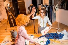 Fashion designer working at the office. Two female multi-ethnic fashion designers working with clothes and drawings at the studiowith different tailoring tools royalty free stock image