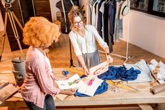 Fashion designer working at the office. Two female multi-ethnic fashion designers working with clothes and drawings at the studiowith different tailoring tools royalty free stock photography