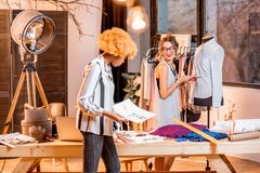 Fashion designer working at the office. Two female multi-ethnic fashion designers working with clothes drawings standing at the office with different tailoring stock photos