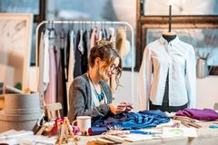 Fashion designer working at the office. Young female fashion designer working with blue fabric sitting at the beautiful office with different tailoring tools on royalty free stock images