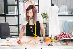 Fashion designer working on sketch in clothing design studio. Stylish fashion designer working on sketch in clothing design studio royalty free stock images