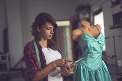 Fashion designer working. Young fashion designer working on a new dress models in her atelier Stock Photos
