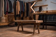 Fashion designer workplace with stylish clothes on hangers and bottle of whisky. On table stock image