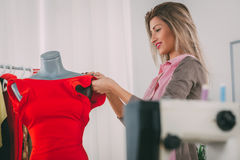 Fashion Designer. Young woman, fashion designer, creates a dress on mannequin. In addition to the mannequin on the table is sewing machine. Selective focus royalty free stock photo