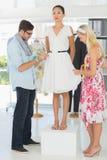 Fashion designers adjusting dress on model Royalty Free Stock Photography