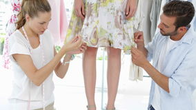 Fashion designers adjusting hemline of dress on a model stock video footage