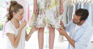Fashion designers adjusting hemline of dress on a model stock footage