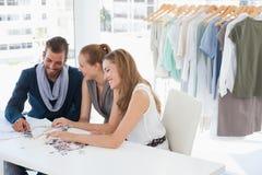 Fashion designers discussing designs in studio Stock Photo