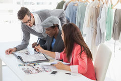 Fashion designers discussing designs in studio Royalty Free Stock Images