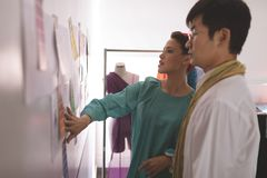 Fashion designers discussing over designer sketch on wall in design studio. Side view of fashion Multi-ethnic designers discussing over designer sketch on wall stock image