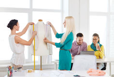 Fashion designers measuring jacket on mannequin Royalty Free Stock Images