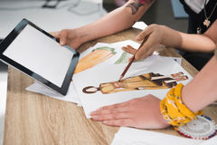 Fashion designers working with blueprints and digital tablet royalty free stock photos