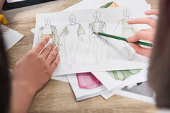 Fashion designers working with blueprints of models stock images