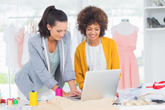 Fashion designers working on a laptop Royalty Free Stock Photo