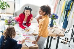 Fashion designers working with sketches. High angle view of smiling young multiethnic fashion designers working with sketches at workplace royalty free stock image