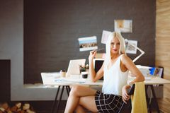 Fashion designers working in studio sitting on the desk. stock photos