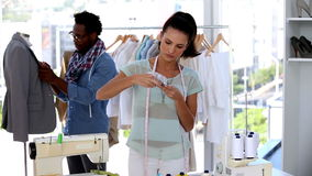 Fashion designers working together on a jacket. In their studio stock footage