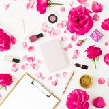 Fashion desk composition with cosmetics - lipstick, eye shadows, nail polish, pink roses flowers and clipboard, notebook, pen on w. Hite background. Flat lay royalty free stock images
