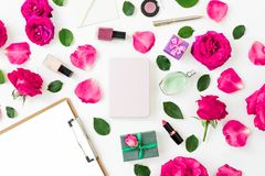 Fashion desk with cosmetics - lipstick, eye shadows, nail polish, pink roses and clipboard, notebook, pen on white background. Fla. T lay, top view royalty free stock images