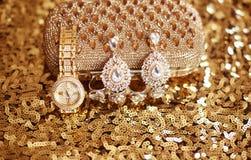 Fashion diamond earrings and golden wristwatch, womens accessori Stock Image