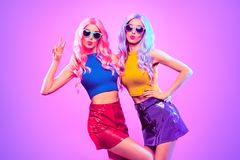Fashion. Disco Party girl dance in neon light. Gorgeous Disco Party girl with Kiss Face Having Fun. Pink Purple hairstyle. High Fashion. Two young beautiful stock image
