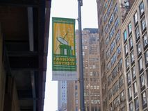 Fashion District banner in a city. Green yellow and white Fashion District banner on a pole with tall buildings in the background royalty free stock images