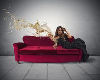 Fashion drink. Beautiful girl drinking wine on a red sofa Royalty Free Stock Image