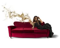 Fashion drink. Beautiful girl drinking wine on a red sofa Royalty Free Stock Photos