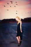 Fashion in dusk. Blond fashion model in short black dress and punk hairstyle outdoor shot at dusk Stock Photography