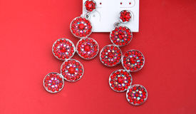 Fashion earings on red background Royalty Free Stock Images