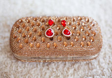 Fashion earrings style red jewels with diamonds on golden purse Stock Photos